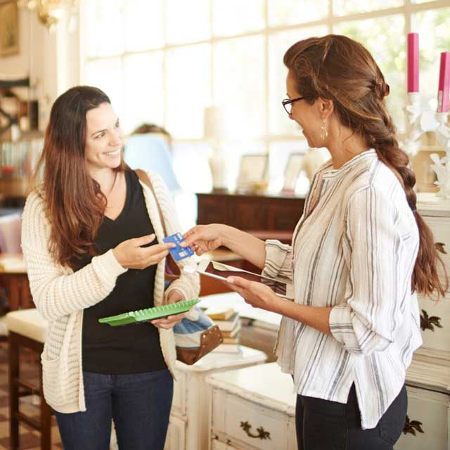 Woman merchant handing customer her card after completing sale.