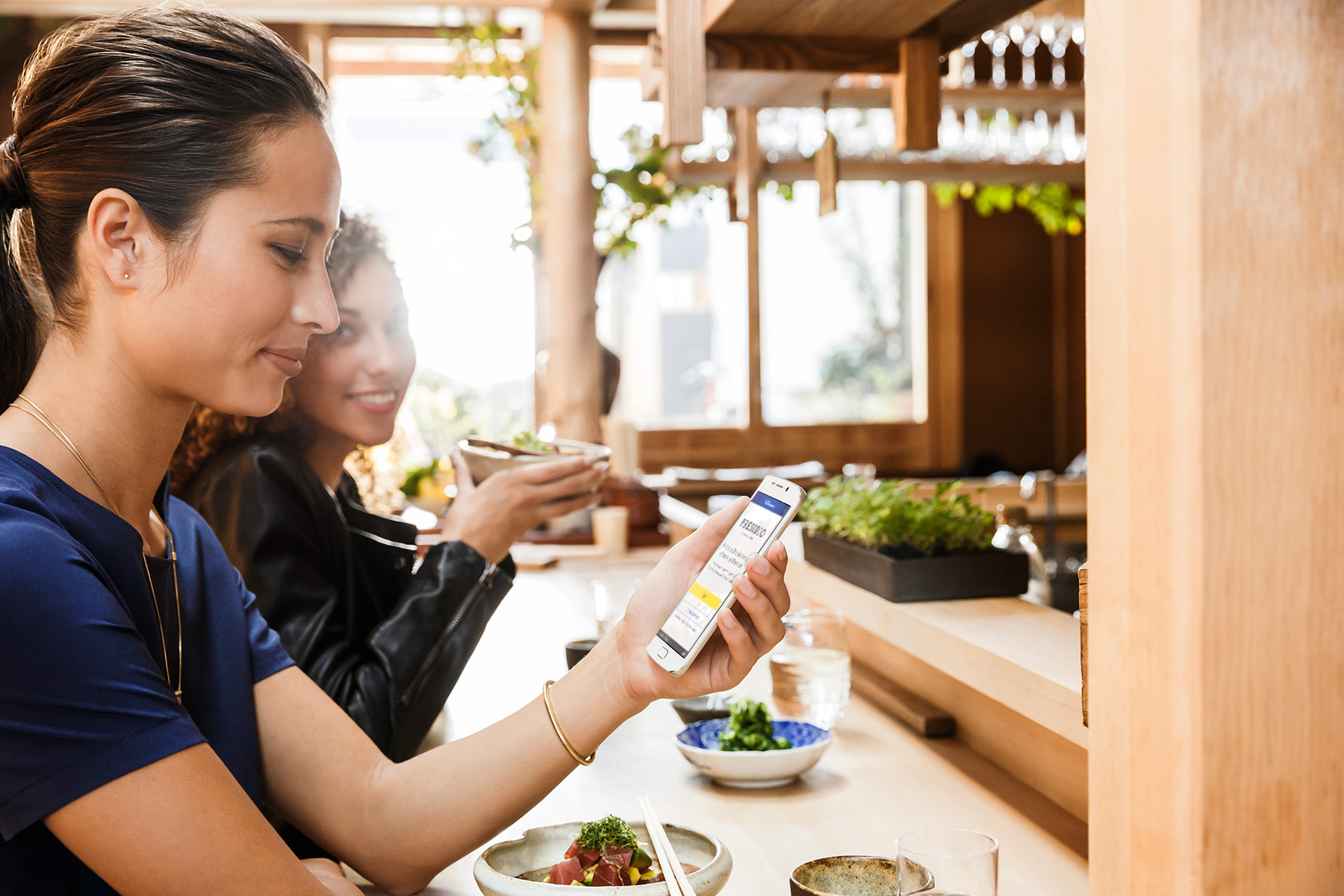 Women eating while holding a mobile phone