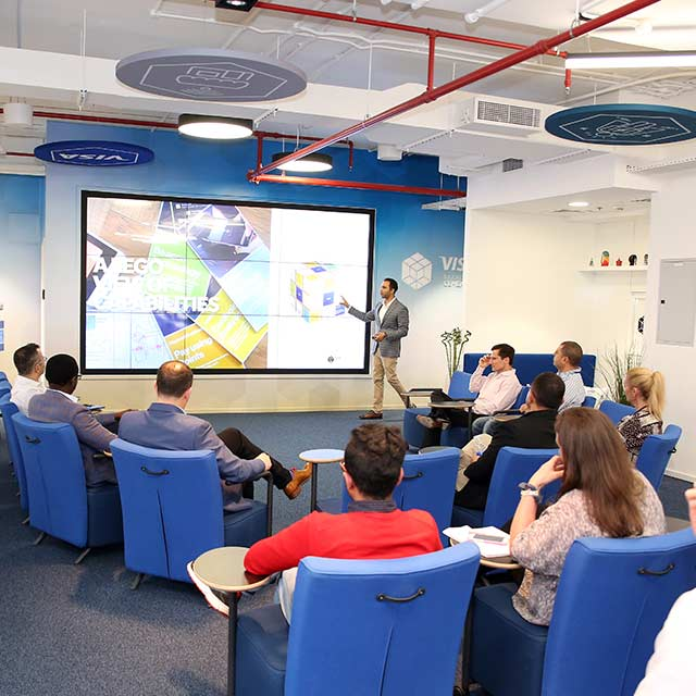 A Visa employee using a big screen display for a presentation in the Collaboration Space.
